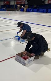Olympic Oval operations team prepare the ice by painting lines on it