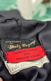 """Label on a donated robe that reads """"Donated by members of the Alberta Bar and Bench."""""""