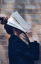 School Girl with Book in front of natural rustic red brick background holding book up to her face